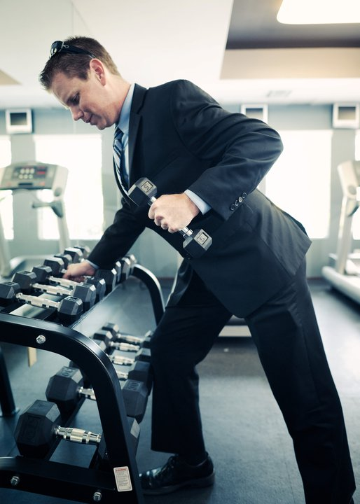 man on treadmill carrying weight wearing business suit